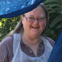 A White woman with glasses and a big smile wearing an apron, looking between two pieces of blue cloth.
